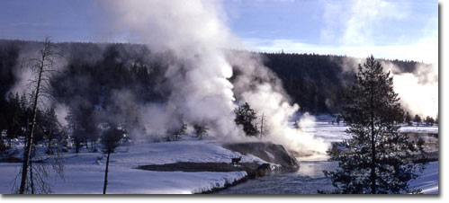 Steam rises from geysers in Yellowstone National Park in a deep and dark December.